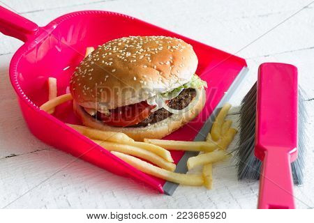 Sweeping junk food with burger french chips and dustpan concept of health detox diet