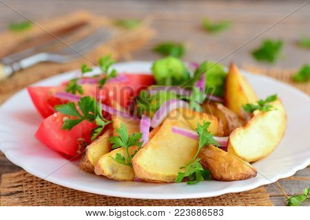 Roasted potatoes and vegetables. Roasted potato wedges, boiled broccoli, fresh tomato slices, red onion, green parsley on a serving plate and on a wooden background. Vegetarian entree recipe. Closeup