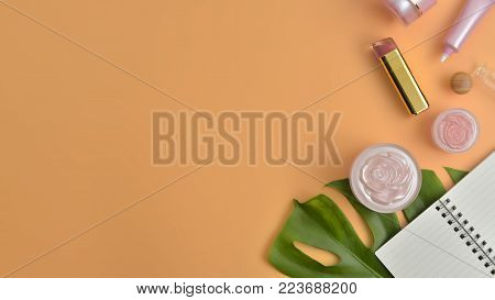 Blank label cosmetic products and green leaves on brown color background. Natural beauty products for branding mock-up concept.