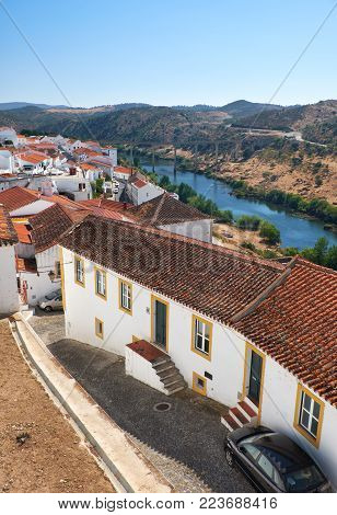 The view of tile roofs of Mertola with bridge across the valley of Guadiana river on the background. Mertola. Portugal
