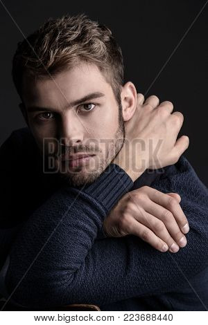 Handsome young man in scarf and sweater. Studio portrait. Autumn and winter clothing. Male fashion.