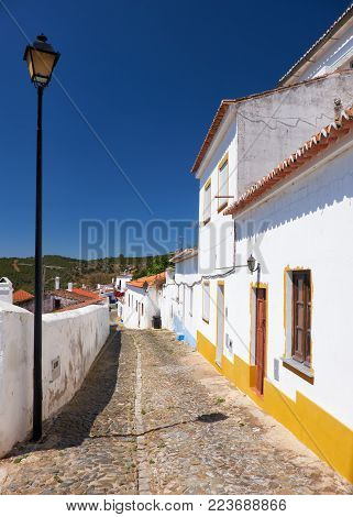 The cozy narrow paved streets with white Alentejo country-style houses inside the old city walls of Mertola. Baixo Alentejo. Portugal