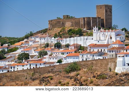 The mediaeval castle on the top of the hill surrounded by residential Alentejo country-style houses inside the old city walls of Mertola.