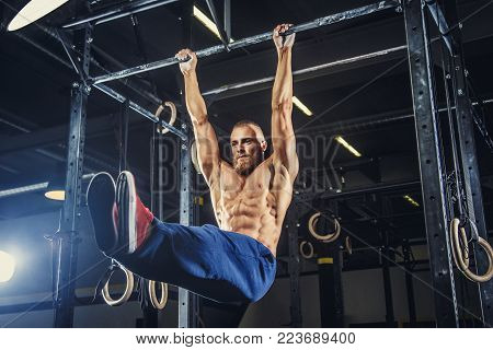 Muscular shirtless man doing pulling up on horizontal bar.