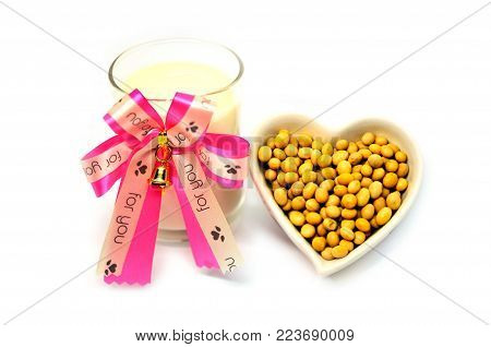 Glass soy milk width ribbon and Soy bean in heart shape for valentine festival isolated on white background, food and drink healthy concept