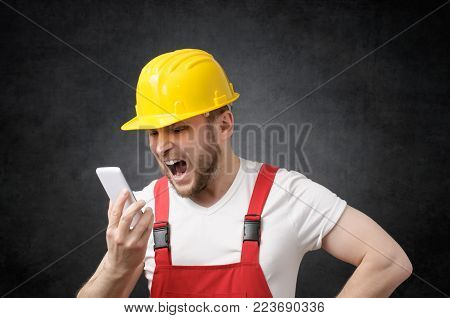 Portrait of an angry worker shouting on the phone