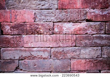 An old brick wall. The background is made of bricks. Pattern of the structure of a brick wall with masonry. Old wall European home