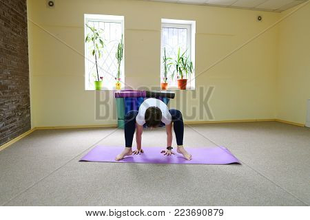 Beautiful young woman of American origin stands in middle of room on yoga mat and performs asanas standing on one leg. Girl dressed in sporty black tights and white T-shirt, hair is black and short cut. Concept of healthy lifestyle, in care of physical he