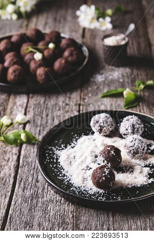 Homemade healthy vegan chocolate balls, truffles, candies sprinkled grated coconut in the plate on the vintage wooden table. Selective focus. Haze effect