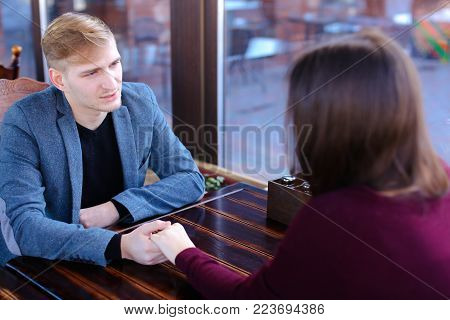 Boyfriend want to make girlfriend offer of hand and heart in favorite cafe, couple waiting for order and fooling. Young fair-haired woman with neat red manicure and guy in blue jacket sitting near wooden table. Concept of cozy luncheonette and nice atmosp