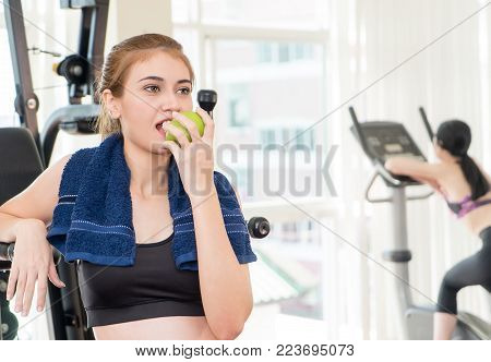 Healthy woman is eating apple fruit in fitness gym