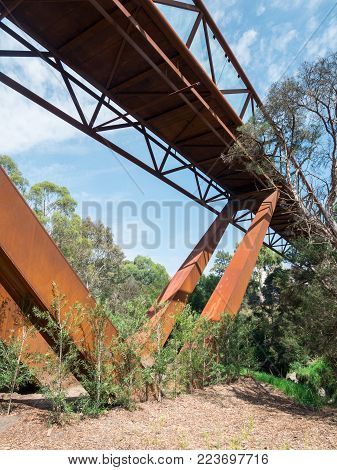 Melbourne, Australia - January 26, 2018: elevated walkway crossing Gardiners Creek connecting two parts of the Deakin University Burwood campus. Construction of the footbridge was controversial.