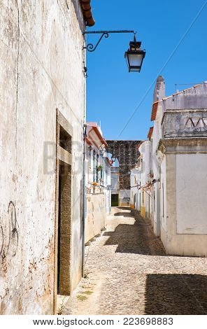 The view of cozy narrow street of Evora with the stone aqueduct of Silver Water (Prata Aqueduct)  on the background. Evora. Portugal