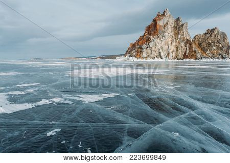 Rock formation over mountain lake with ice covered water surface,  Russia, Lake Baikal
