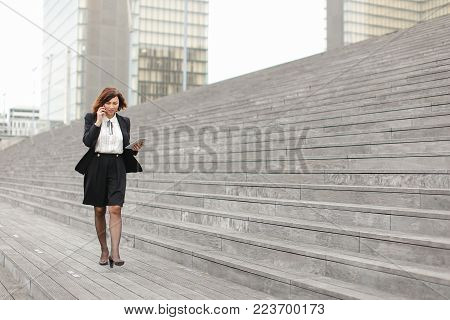Asian appearance business woman walk along broad stairs by   and smiling speaking by phone. In hand female hold small white tablet. Lady dressed in white blouse, black jacket and skirt. Concept of telephone conversation on go.
