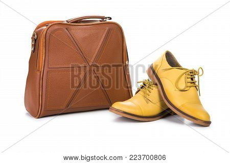 Pair of women shoes and handbag isolated over white.
