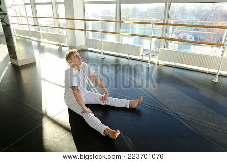 HR manager bragging of training results in gym, guy implement sport plan and showing achievement on camera. Young tattooed man sitting on parquet floor not far from ballet barre showing muscle. Concept of sportswear, big hall or place for individual train