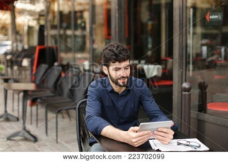 Dissatisfied man losing at online game playing with tablet at street cafe. Young man has dark hair, brown eyes and beard. Concept of excitement loss and Internet entertainments.