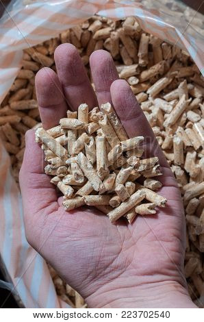 Hand holding ecological wood pellets for heating. Vertical composition.