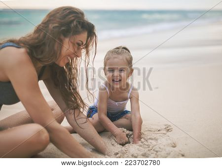 Mom and happy baby playing near the beach. Traveling with your family, child. Games with child affect early development. Important to spend enough time with your kids.