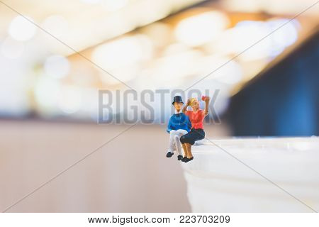 Miniature people : Couple sitting on cup , Valentine day's concept