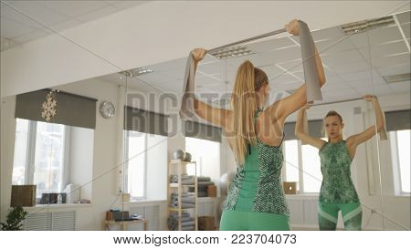 the girl is engaged in pilates. The girl is pulling the ribbon. The girl's back. A girl with a beautiful back. Girl with Delta Muscles