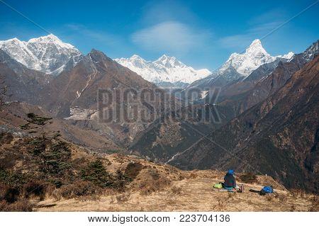 man sitting and looking at Ama Dablam mountain in Nepal, Sagarmatha, November 2014
