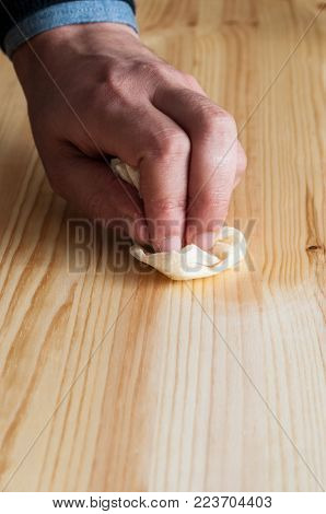 Hand oiling a wood Surface. Vertical composition.
