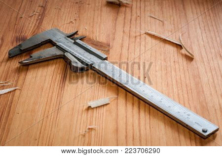 A Vernier caliper on a wooden table