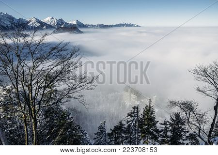 scenic view of snowy mountains in fog near Neuschwanstein Castle, Germany
