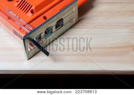 An orange elctric jig saw on a work table