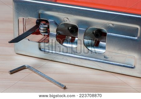 An electric jig saw and a hex key on a wood table