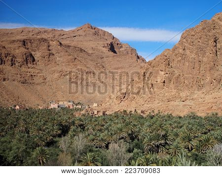 Old town of Tinghir, green palm oasis and rocky Atlas Mountains range landscape in southeastern Morocco with clear blue sky in 2017 warm sunny winter day, Africa on February.