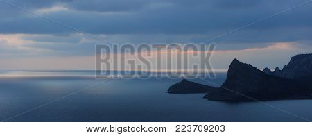 The Crimean landscape. Night panorama with view on rocky capes at sunset on Black sea. The Kapchik cape and the Koba-Kaya mountain in Novy Svet, Crimea.