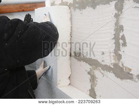 Builder installing rigid styrofoam insulation board for energy saving. Rigid extruded polystyrene insulation.