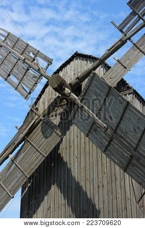Wooden windmill. The ruined blades of the old creaking windmill against a blue sky showed close-up. The windmill is located on the banks of the Dnieper river in Ukraine.