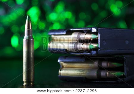 AR-15 ammo and two metal magazines on a green background