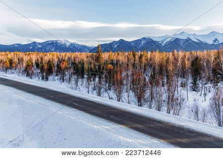 beautiful winter road with trees and snow covered mountains, russian federation