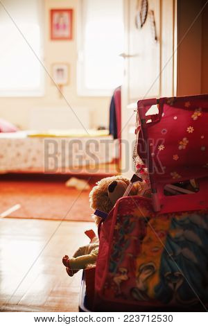 Closeup view on child's toys in basket in front of bedroom during day. Ordinary lifestyle concept.