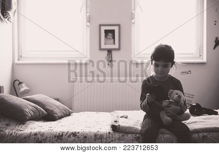 Small girl and bear toy playing and posing.