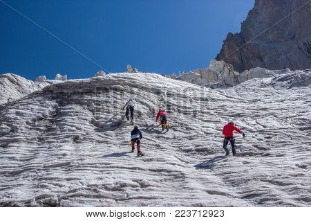 back view of hikers climbing at beautiful snow capped mountains, kyrgyzstan, ala archa