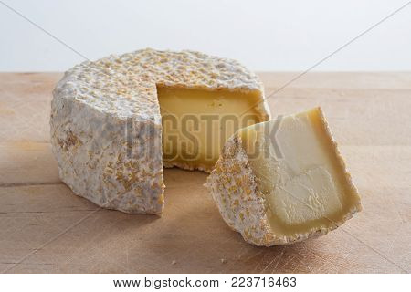 Artisanal cheese made of goat's milk on a wooden cutting board.
