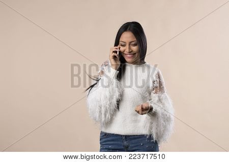 young smiling arabic latina woman talking on the phone isolated on studio background