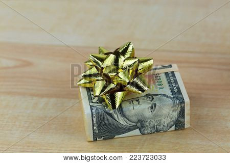 United stated dollar money banknote bill decorated with shiny golden gift ribbon, present box on wooden background