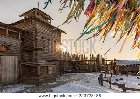 Ancient wooden fortress at sunset. Developing multi-colored ribbons. Wooden fortress in winter. Russia, Suzdal. Gold ring.