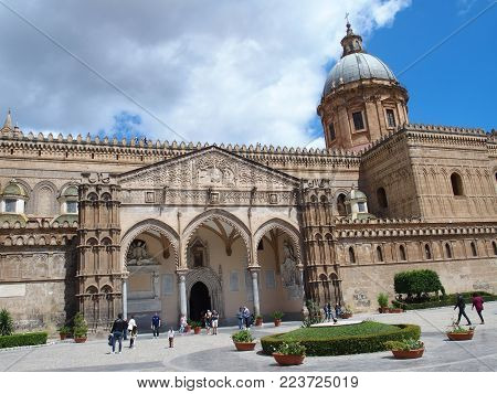 PALERMO, ITALY EUROPE on MAY 2016: Medieval cathedral church at square in center of italian city at Sicily with towers and tourists in front of building, cloudy blue sky in warm sunny spring day.
