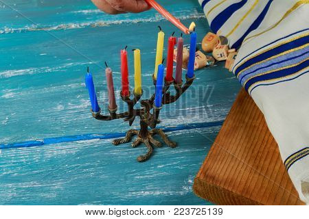 Selective focus of the Hanukkah Jewish holiday with traditional menorah, donuts and wooden dreidel