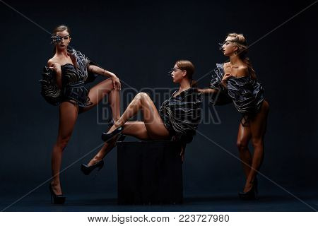 Beautiful sexy go-go performers isolated on black. Sexy girl dance group posing in black underwear. Three strippers.