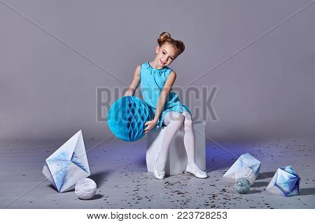 Pretty girl in an elegant blue dress for teenage girls with a make-up. Origami and minimalism. Fashion kid. Designer collection. Charming teenager girl in studio holds an origami figure. Free space for text and advertising. Studio shot.