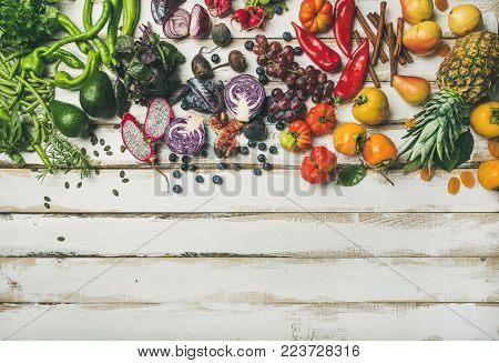 Helathy raw vegan food cooking background. Flat-lay of fresh fruit, vegetables, greens and superfoods over white wooden table, top view, copy space. Clean eating, alkaline diet, vegetarian concept